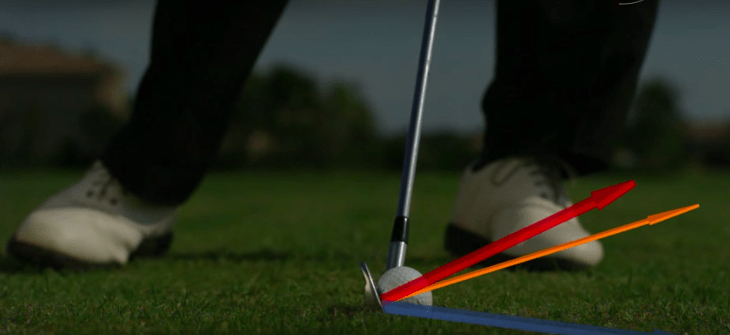 The ideal iron impact is a combination of the club head travelling downwards (blue arrow) with a slightly de-lofted club face (red arrow). Adapted from trackman.
